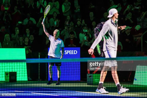 Musician Mike McCready and John Isner of the United States enter the tennis court at the Match For Africa 4 exhibition match at KeyArena on April 29,...