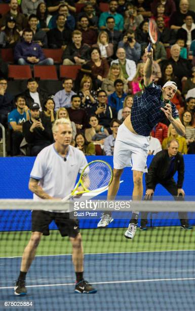 Musician Mike McCready and John Isner of the United States in action against Bill Gates and Roger Federer of Switzerland at the Match For Africa 4...