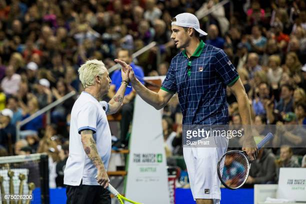 Musician Mike McCready high fives John Isner of the United States at the Match For Africa 4 exhibition match at KeyArena on April 29, 2017 in...