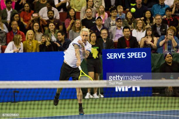 Musician Mike McCready serves against Bill Gates and Roger Federer of Switzerland at the Match For Africa 4 exhibition match at KeyArena on April 29,...