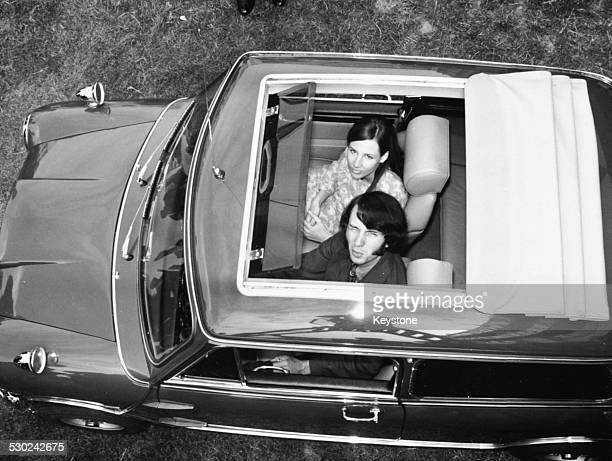 Musician Mike Nesmith of pop band 'The Monkees' peering out of the roof of his Mini with his girlfriend July 3rd 1967