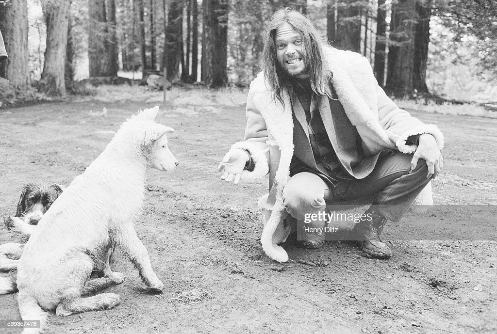 Musician Neil Young jokingly offers his dog a cigarette.