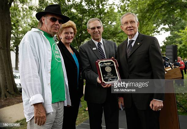 Musician Neil Young US Sen Debbie Stabenow National Farmers Union President Roger Johnson and Senate Majority Leader Harry Reid present Reid with the...