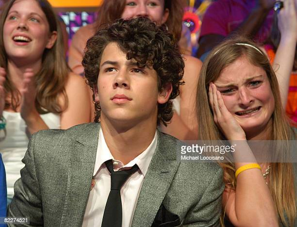 Musician Nicholas Jonas of The Jonas Brothers sits with a fan during MTV's 'TRL' at MTV studios on August 12 2008 in New York City