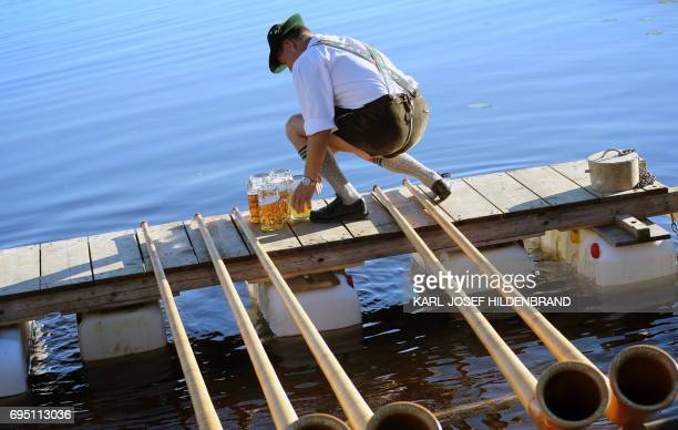 A musician of the alphorn band 'Holdersberger AlpTraumBläser' prepares to perform on a raft floating on the Elbsee lake near Aitrang southern Germany...