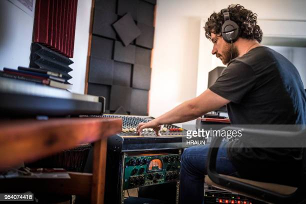 musician operating sound mixer in recording studio - producer stock pictures, royalty-free photos & images
