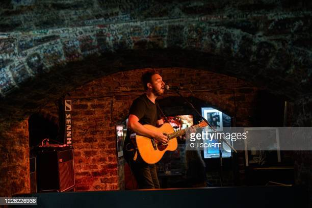 Musician Paul Jones plays Beatles songs to the audience in the Cavern Club as it reopens to the public with live music to host their annual...