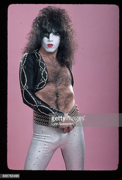 Musician Paul Stanley of the glamrock band Kiss poses in his makeup He is wearing a cropped rhinestonestudded jacket no shirt and tight silver pants...