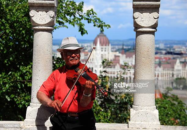 A musician performs at Buda Castle with a view the Parliament building across the Danube river on May 30 2010 in Budapest Hungary Budapest is a large...