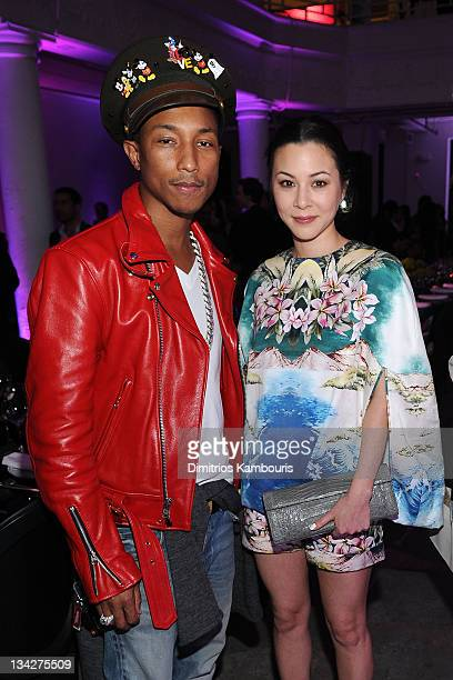 Musician Pharrell Williams and China Chow attend the Dior popup shop featuring Anselm Reyle for Dior at Miami Design District on November 29 2011 in...