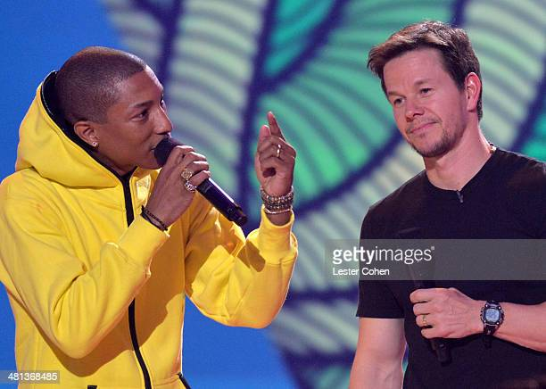 Musician Pharrell Williams and host Mark Wahlberg speak onstage during Nickelodeon's 27th Annual Kids' Choice Awards held at USC Galen Center on...