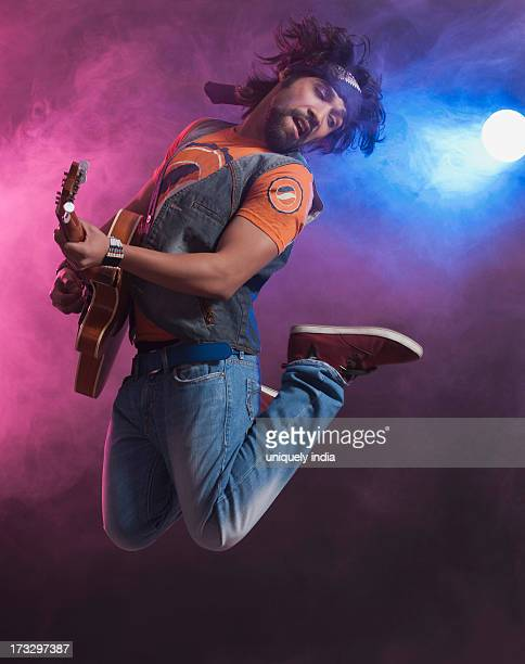 Musician playing a guitar and jumping
