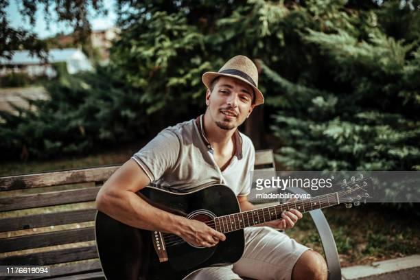 アコースティックギターを弾くミュージシャン - 爪弾く ストックフォトと画像