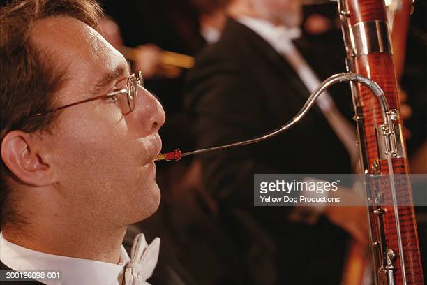 musician playing bassoon in orchestra, side view, close-up - bassoon stock pictures, royalty-free photos & images