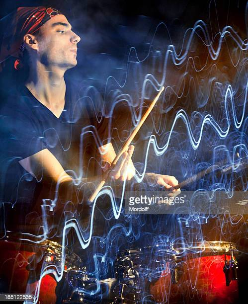 Musician playing drums in dark with pulsating light trace