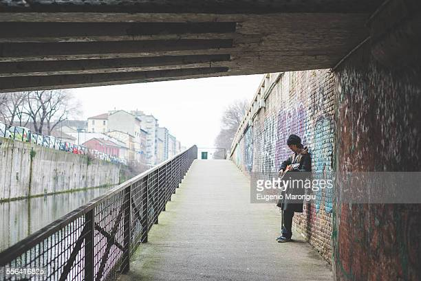 Musician playing guitar by canal wall, Milan, Italy