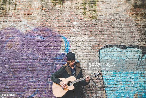 musician playing guitar by canal wall, milan, italy - busker stock pictures, royalty-free photos & images