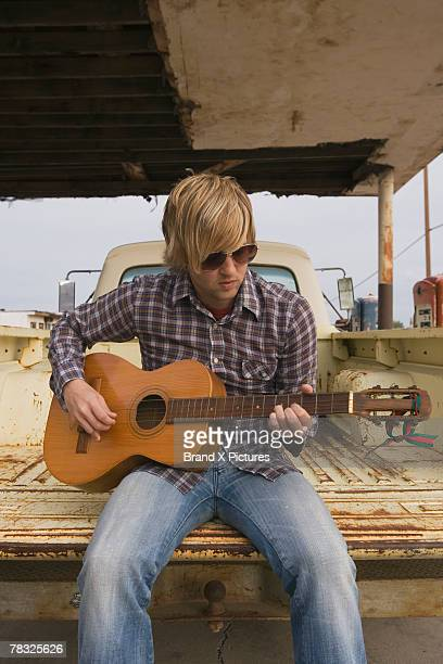 Musician playing guitar in back of pickup truck