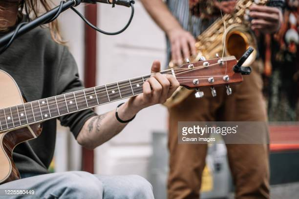 musician playing guitar in the middle of the street in front of a microphone and with a saxophonist - galway stock pictures, royalty-free photos & images