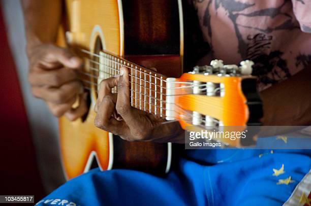 Musician playing guitar on local guitar makers workshop & studio, Mindelo (Porto Grande), Sao Vicente, Cape Verde Islands