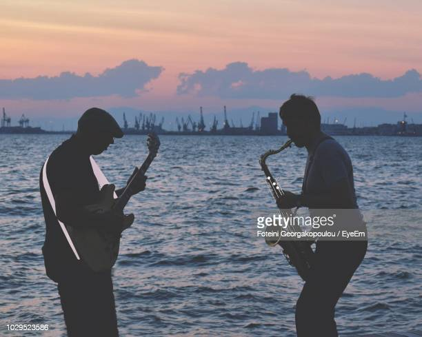 musician playing musical instruments while standing against sea during sunset - thessaloniki stock pictures, royalty-free photos & images