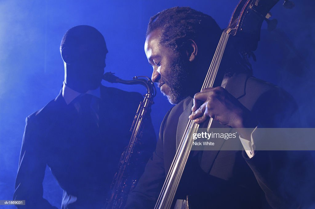 Musician Playing the Double Bass in Front of a Man Playing an Alto Saxophone : Stock Photo