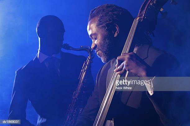 musician playing the double bass in front of a man playing an alto saxophone - performance group stock pictures, royalty-free photos & images