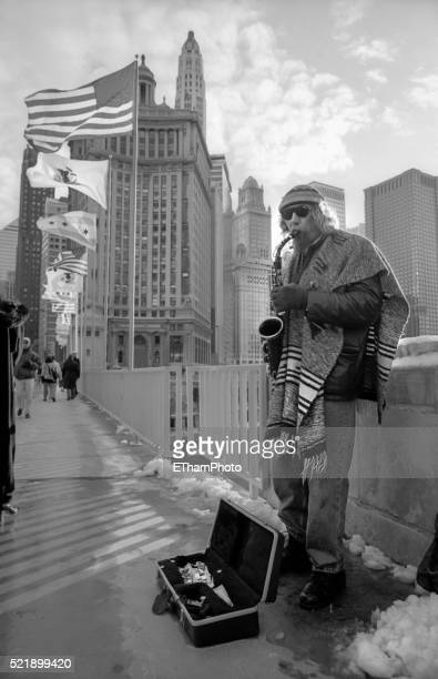 Musician playing the saxophone on Chicago river bridge (1997)