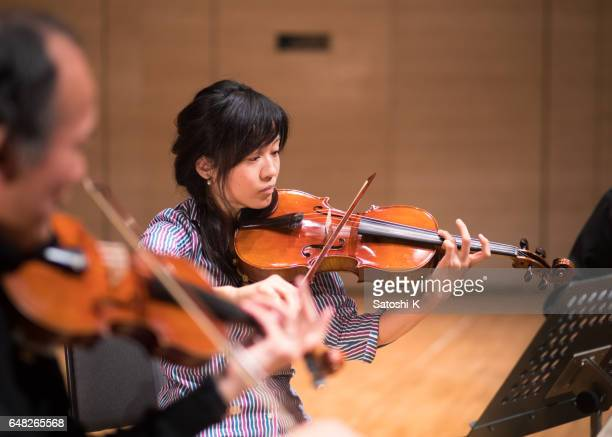 Musician playing violin on concert stage