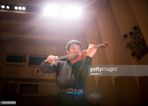 Músico tocando el violín en el escenario del concierto