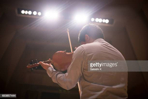 Musician playing violin on stage