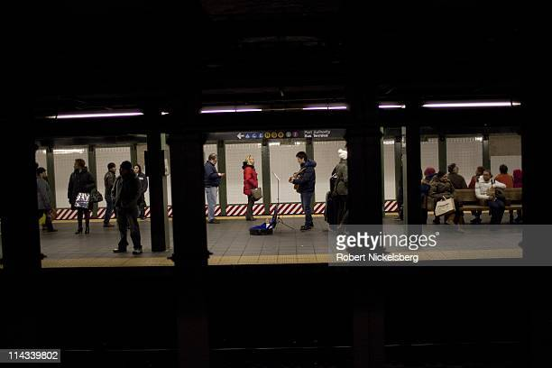 A musician plays a guitar on a subway platform at the Roosevelt Avenue subway station March 26 2011 in Queens New York In 2009 the New York City...