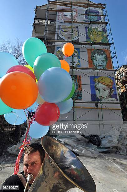 A musician plays in front of a mosaic panel made on a gable end of an apartment house in central Kiev on March 24 2010 during an artprotest action...