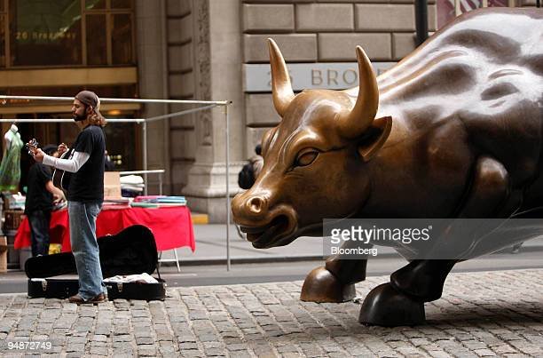 A musician plays next to the Wall Street bull in the financial district of New York US on Monday Oct 13 2008 Stocks rallied worldwide with the...