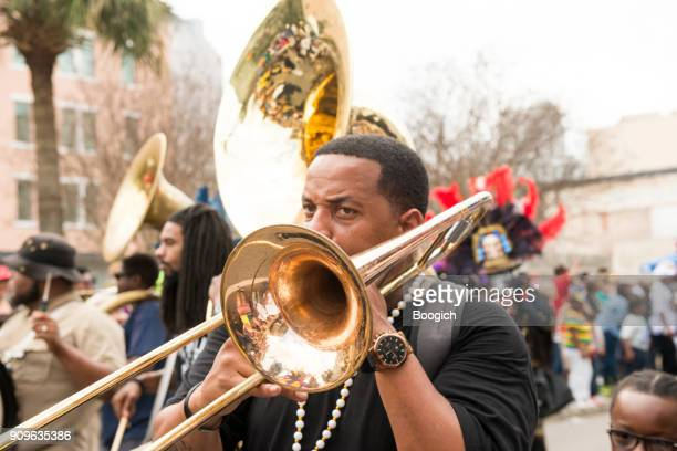musician plays trombone in mardi gras marching band usa - mardi gras new orleans stock photos and pictures