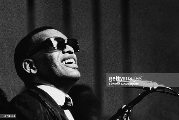 Musician Ray Charles performing at a microphone c 1960