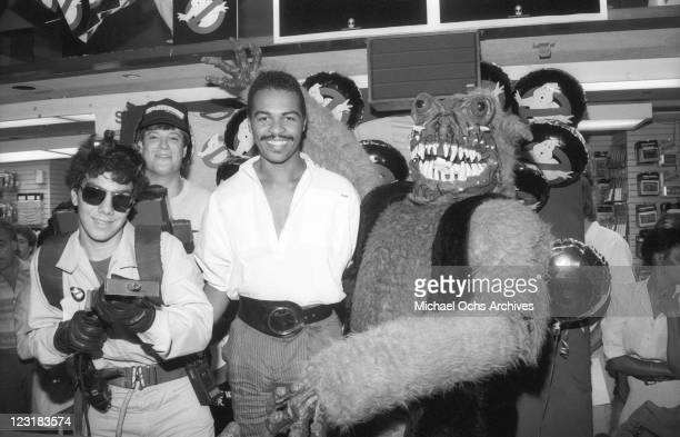 Musician Ray Parker, Jr. Poses with fans dressed as Ghostbusters and ghosts at a Sam Goody record store to promote the release of his single...