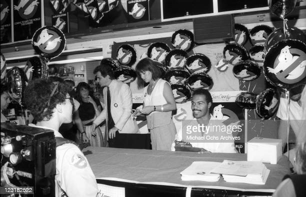 Musician Ray Parker Jr signs an autograph for a fan wearing a Ghostbusters costume at a Sam Goody record store to promote the release of his single...