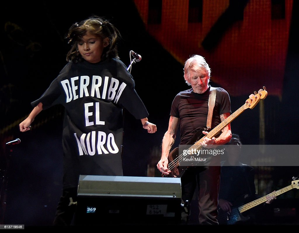 Musician Roger Waters (R) and children's choir singer wearing a T-shirt saying 'derriba el muro' (tear down the wall) performs during Desert Trip at The Empire Polo Club on October 9, 2016 in Indio, California.
