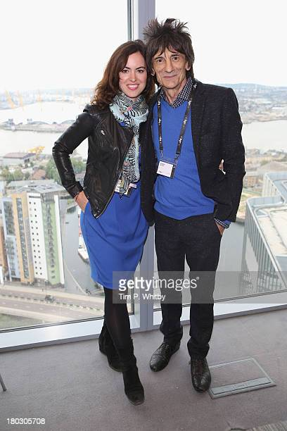 Musician Ronnie Wood and wife Sally Humphreys pose on the trading floor during the BGC Charity Day 2013 at BGC Partners on September 11 2013 in...