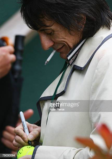 Musician Ronnie Wood signs an autograph during day nine of the Wimbledon Lawn Tennis Championships at the All England Lawn Tennis and Croquet Club on...
