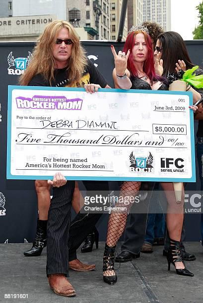 Musician Sebastian Bach and Rocker Mom contest winner Debra Diamant hold first place prize check at America's Hottest Rocker Mom contest in Madison...