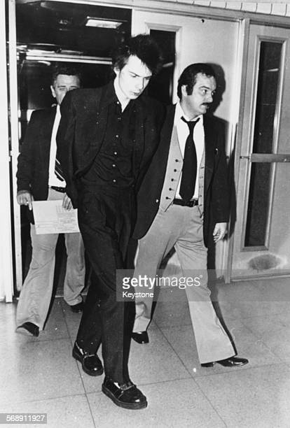 Musician Sid Vicious of the band 'Sex Pistols' is led away in police custody on a charge of murder after his girlfriend Nancy Spungen was found...