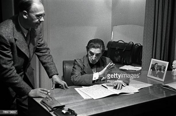 Musician Sir John Barbirolli reading the score of a symphony with William Alwyn in the conductor's room at Free Trade Hall, Manchester after a...