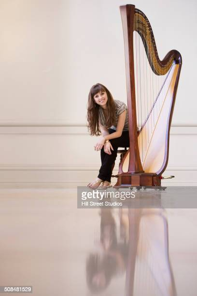 Musician sitting with harp