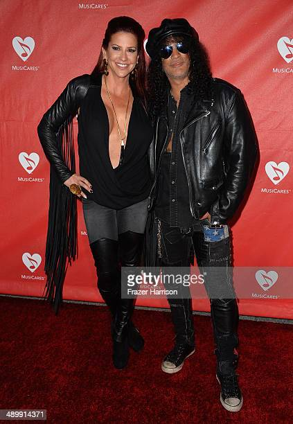 Musician Slash and Perla Hudson attend the 10th annual MusiCares MAP Fund Benefit Concert at Club Nokia on May 12 2014 in Los Angeles California