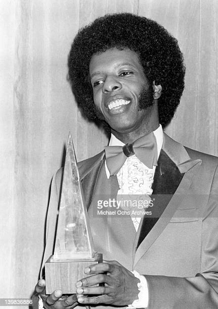 Musician Sly Stone of the psychedelic soul group 'Sly And The Family Stone' poses for a portrait holding an American Muic Award in circa 1974