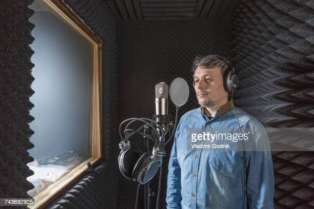 Musician standing by microphone with headphones in recording studio