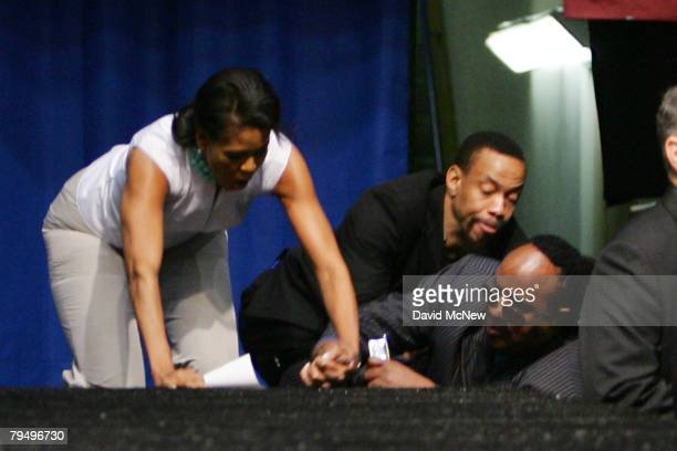 Musician Stevie Wonder falls while ascending backstage stairs with Michelle Obama wife of Democratic presidential hopeful US Sen Barack Obama at a...