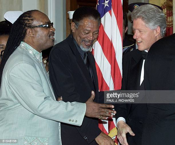 Musician Stevie Wonder reaches past actor Morgan Freeman to shake hands with US President Bill Clinton in the reception line as the Clinton's host a...